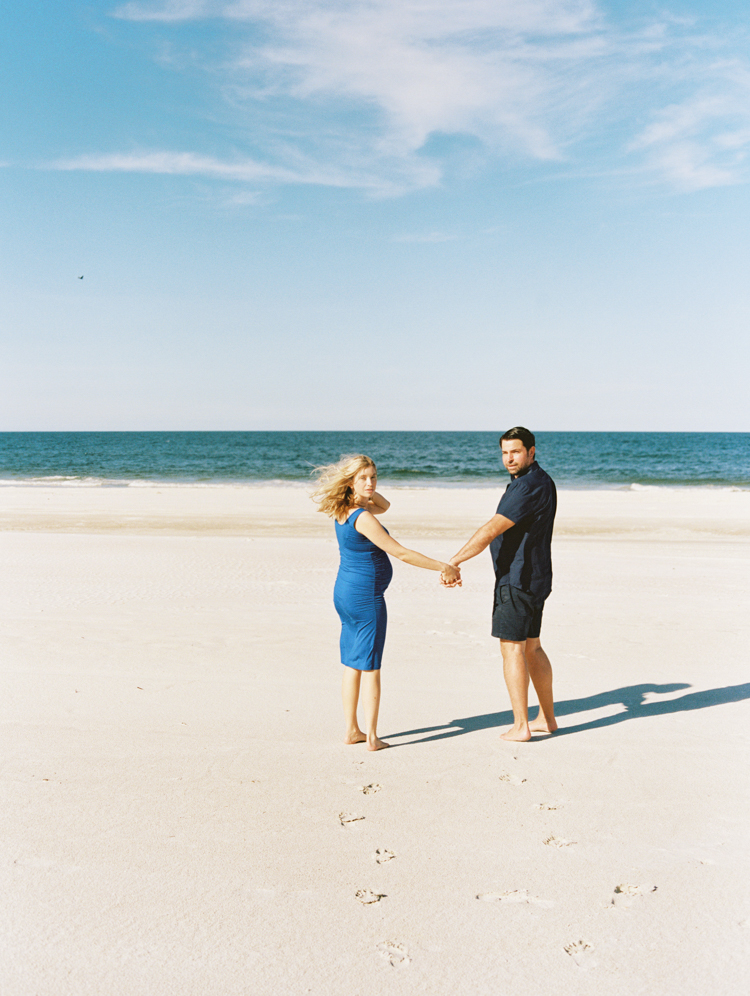 Maternity Photos in New Smyrna Beach featuring couple walking on the beach